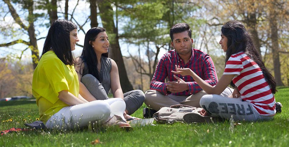 NYIT students sitting and  conversing in a grassy field