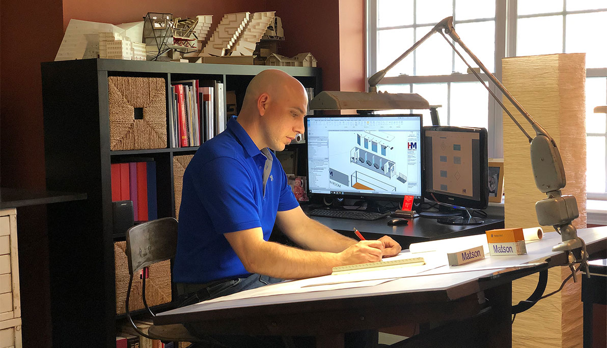 Architect alumnus Erik Fred at work at his drafting desk with a monitor over his shoulder displaying an architectural rendering
