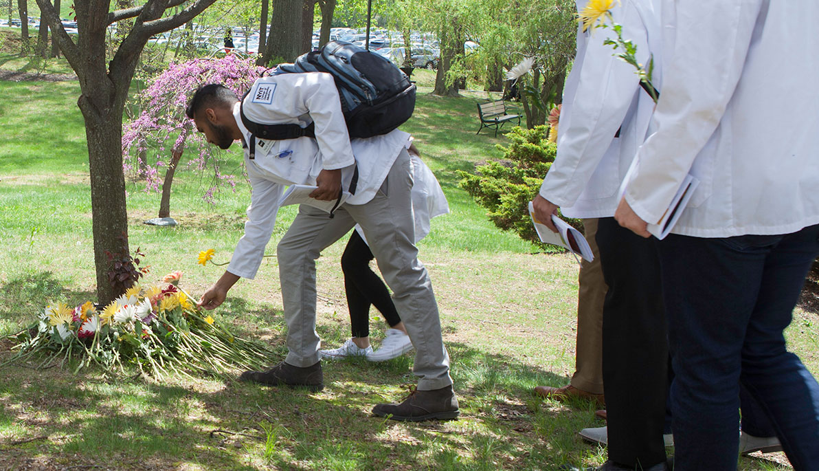 NYIT student placing flower by tree