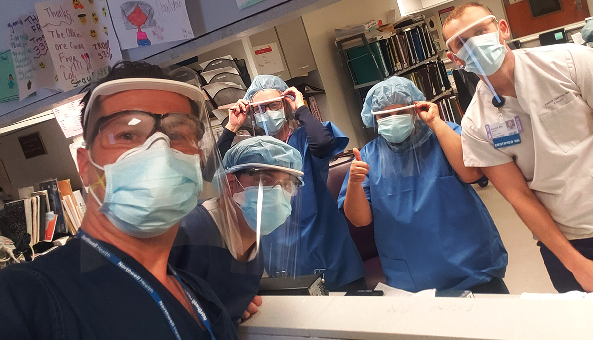 Front-line health care workers in scrubs and New York Tech-manufactured 3-D PPE gear.
