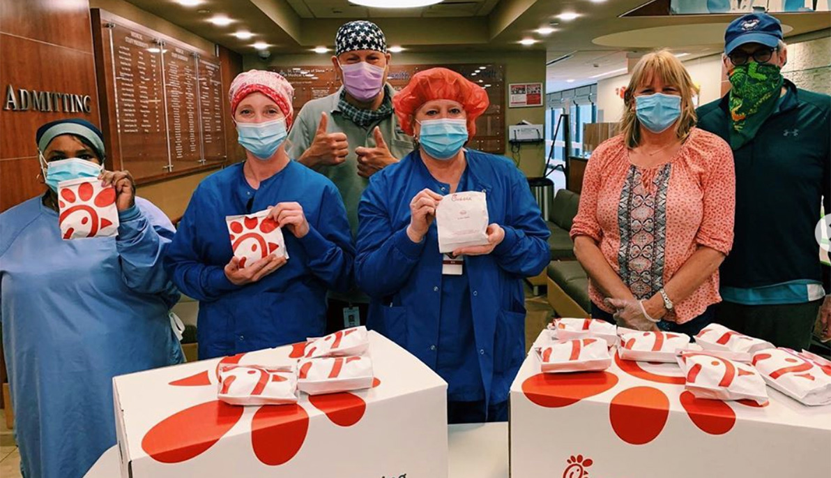 Masked hospital staff posing with food delivered by New York Tech's Help Our Heroes volunteers.
