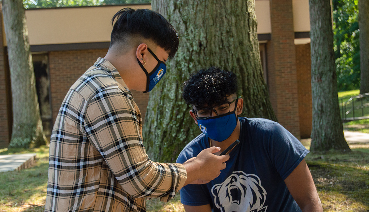 Two students wearing masks looking at phone.