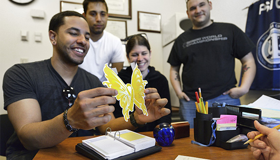 Behavioral Science students holding up a clipart of a butterfly