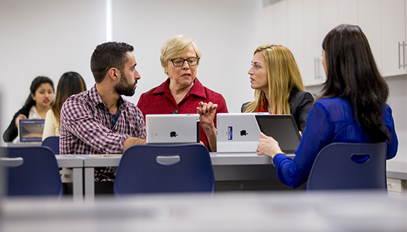 Students and professors in conversation with ipads in front of them