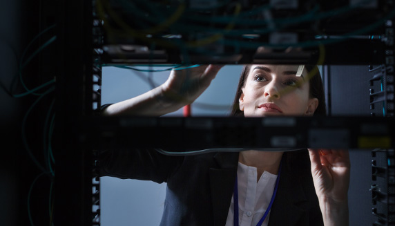 View of young woman through electronic equipment as she checks network wires