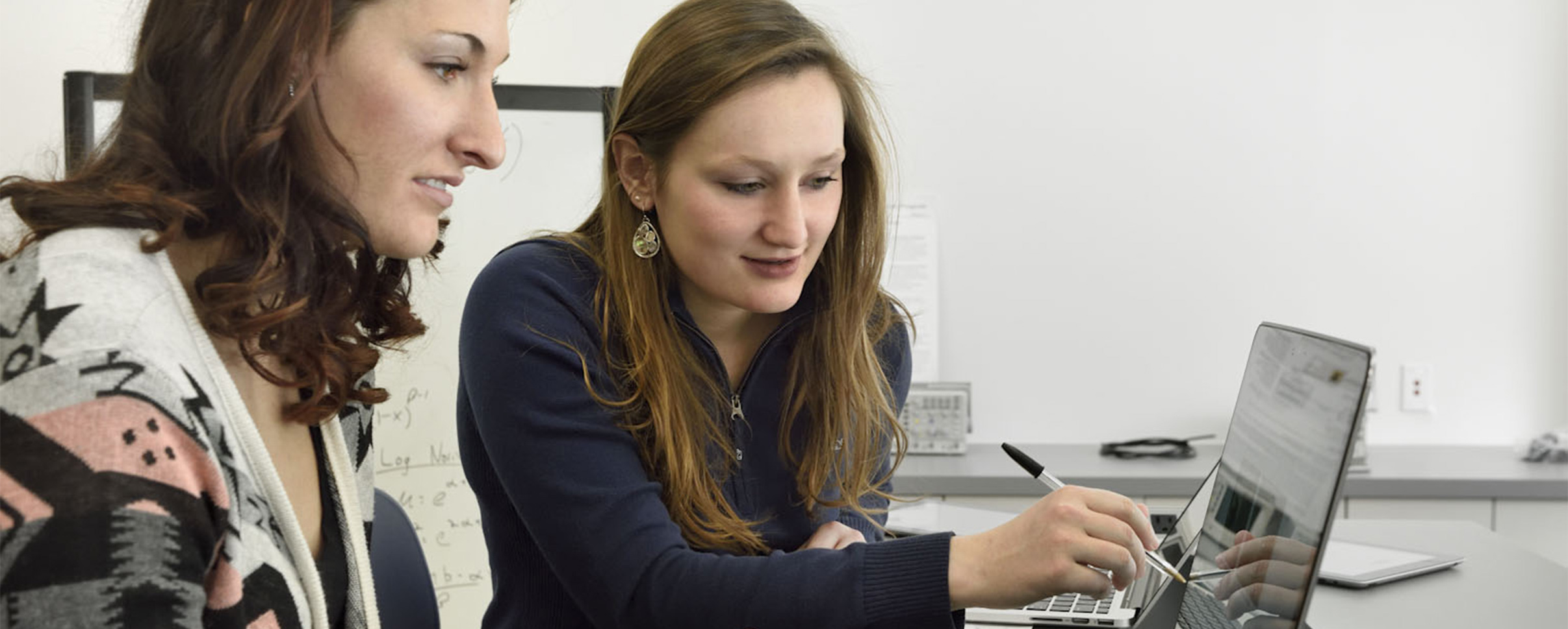 Two students working together on laptops