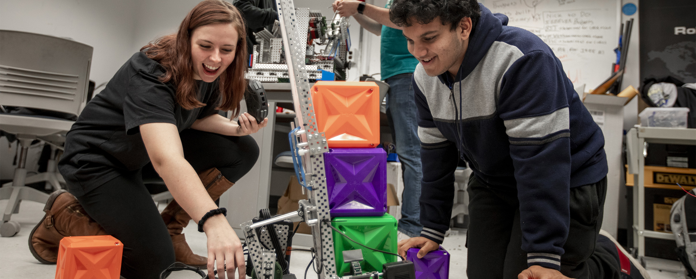 Mechanical engineering students working on project with colorful boxes