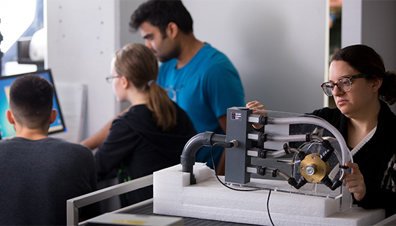 Three graduate mechanical engineering students looking at computer while one works on a different machine