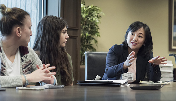 Three women in discussion at a conference table