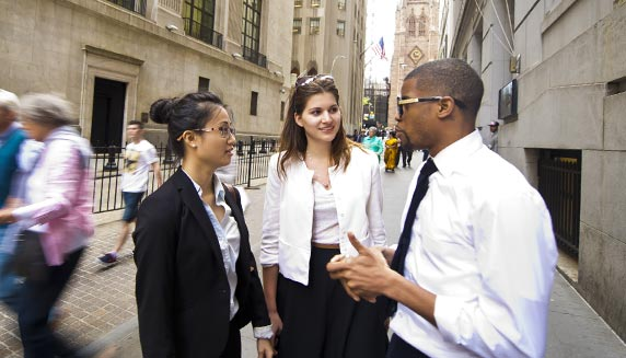 Three business students talking on city street