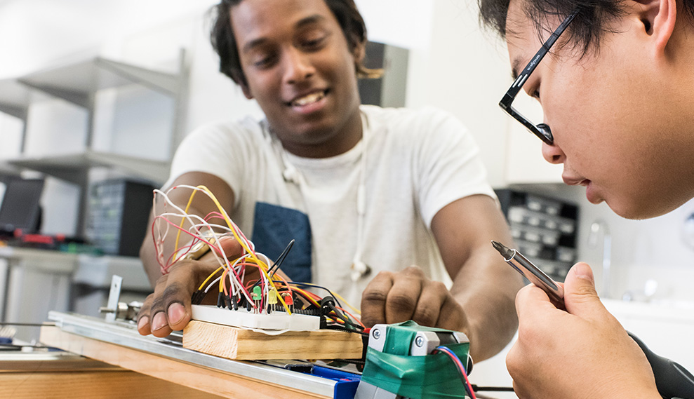 Electrical and computer engineering students working on a circuit board