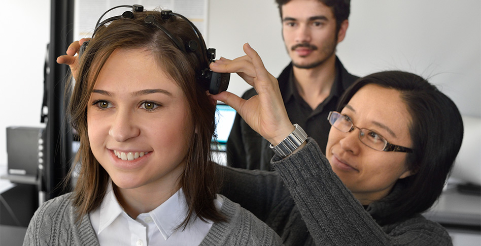 Professor adjusting brainwave monitoring device on head of student