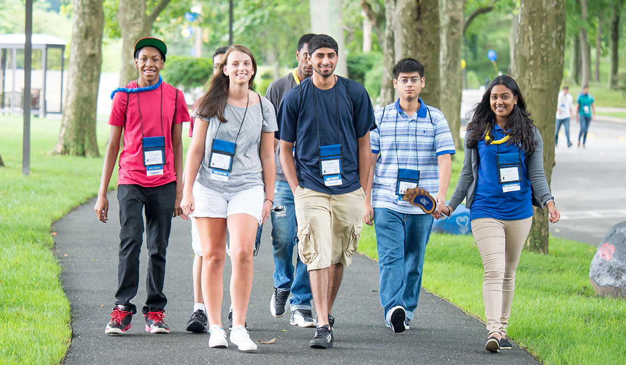 Five NYIT students walking on path on Long Island campus