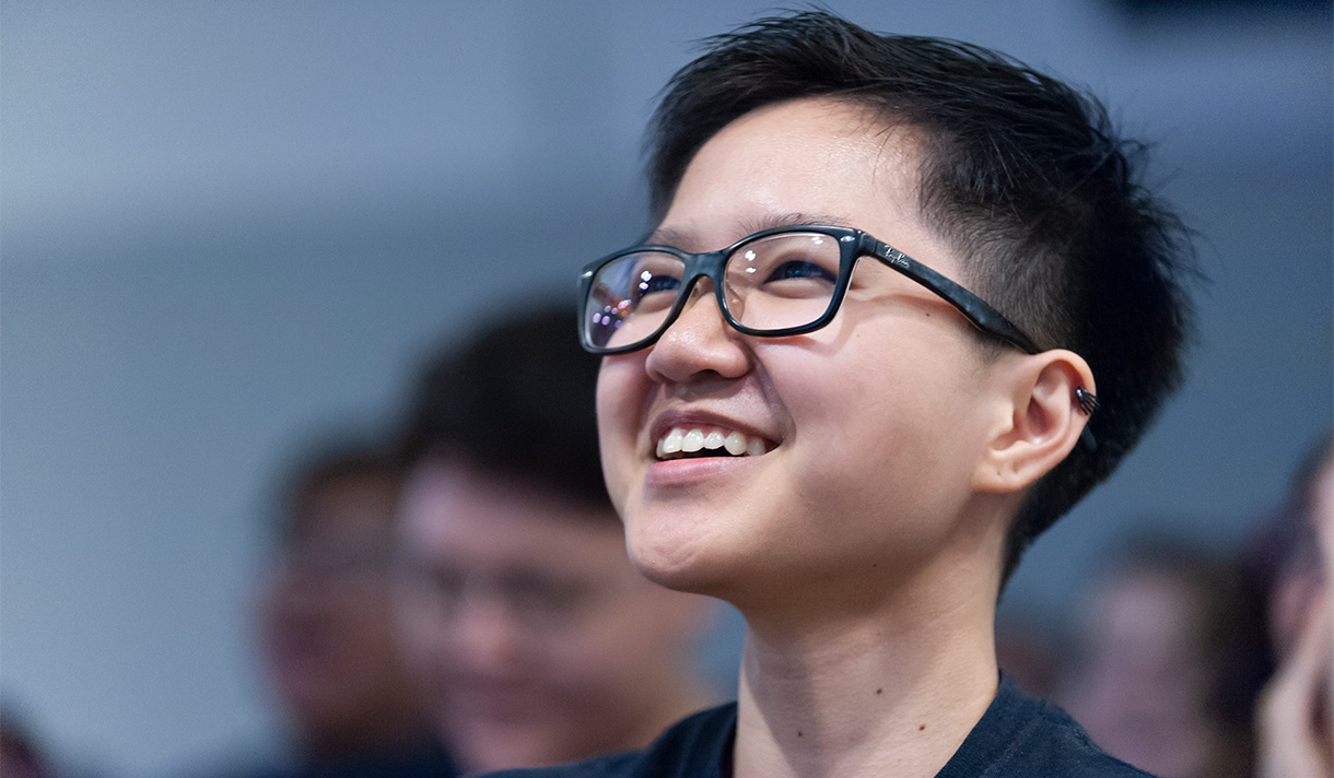 NYIT student with glasses smiling