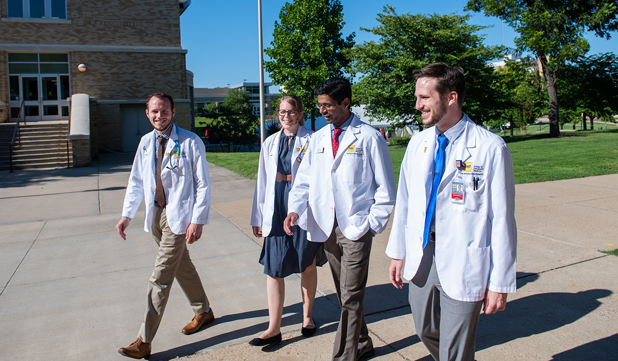 Four medical students walking on campus