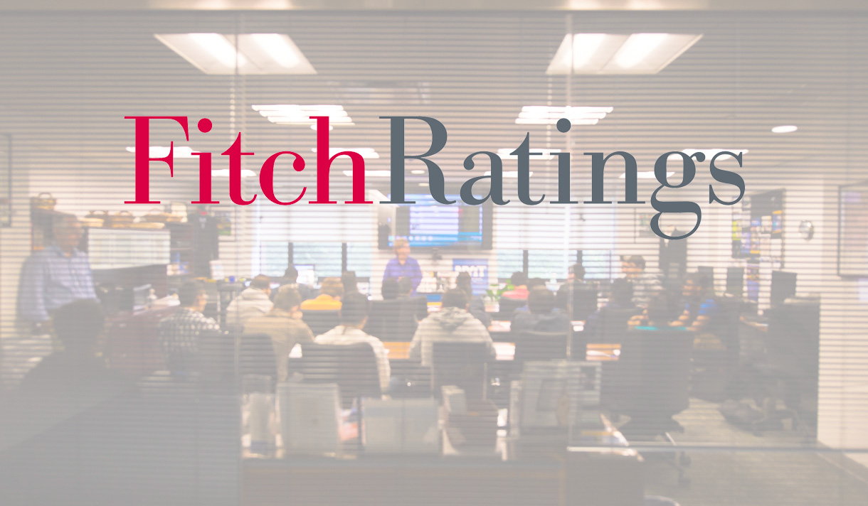 Smiling students in a class for a presentation with Fitch Ratings logo on a transparency.