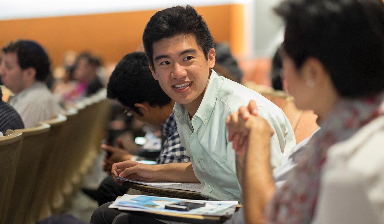 Smiling student talking to another student in lecture hall.