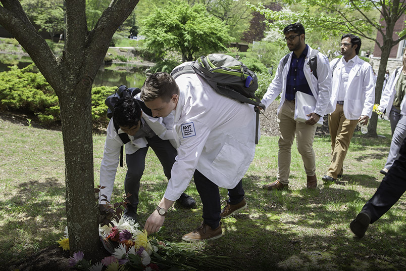 Students place flowers near the base of a newly planted tree dedicated in memory of those who donated their bodies to science.