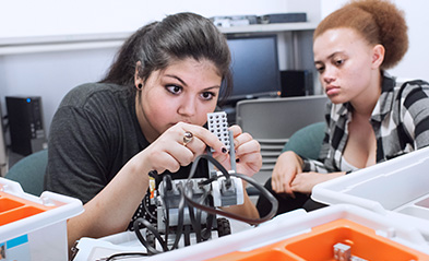 Two female engineering students working on hardware at NYIT