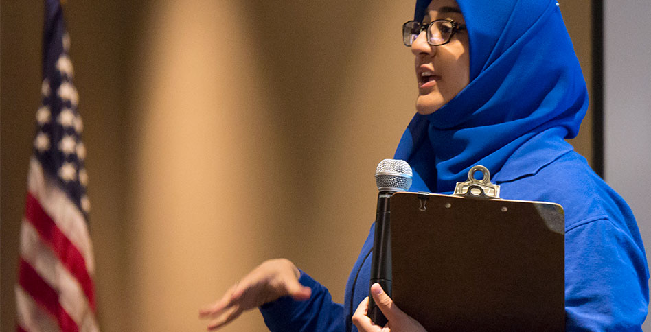 student wearing hijab speaks into microphone while holding clipboard