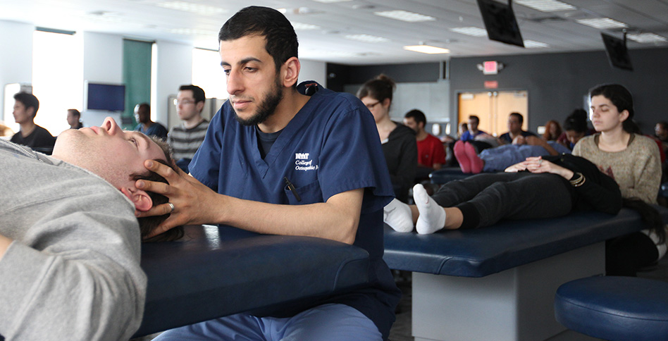 NYITCOM student practicing his skills on a patient