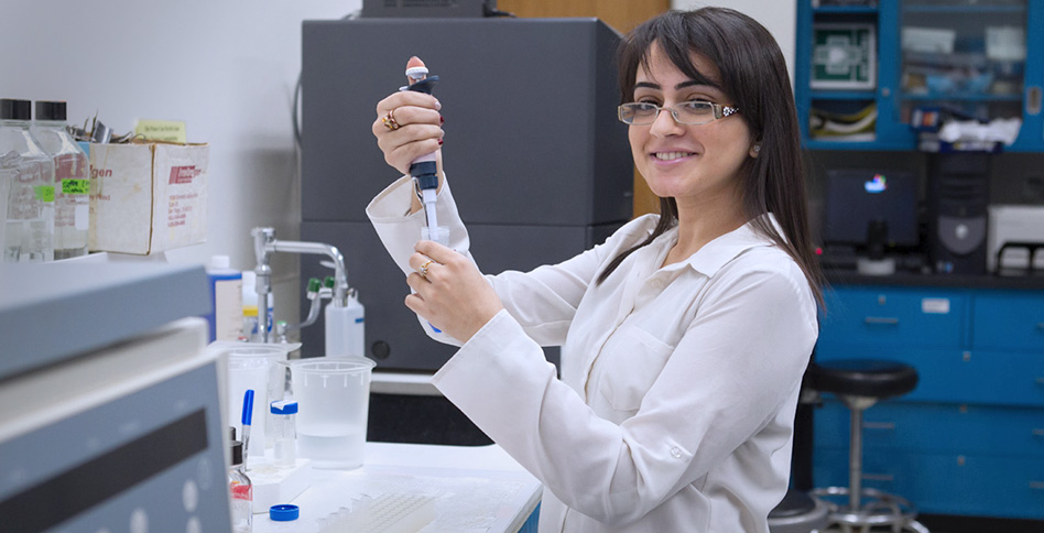 NYITCOM student performing an experiment