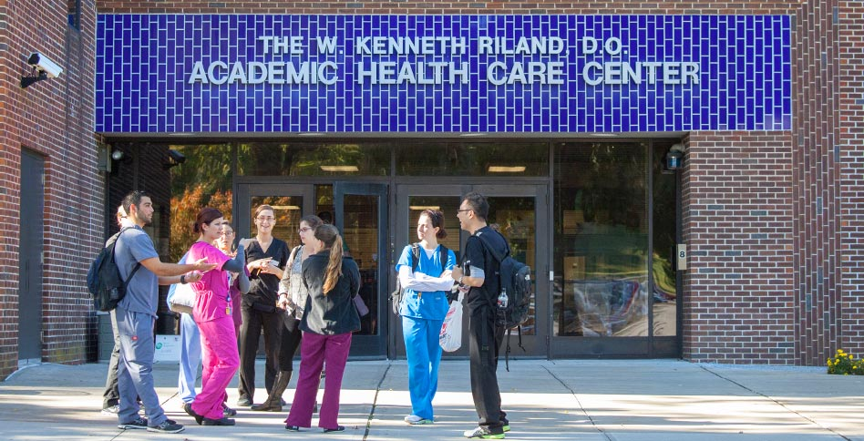 NYITCOM students standing in front of the Riland academic health care center