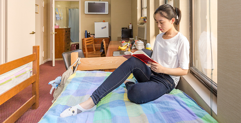female student sits on bed reading in dorm room