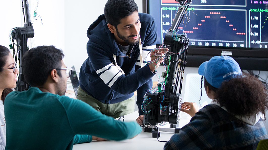 NYIT students working on robotic arm